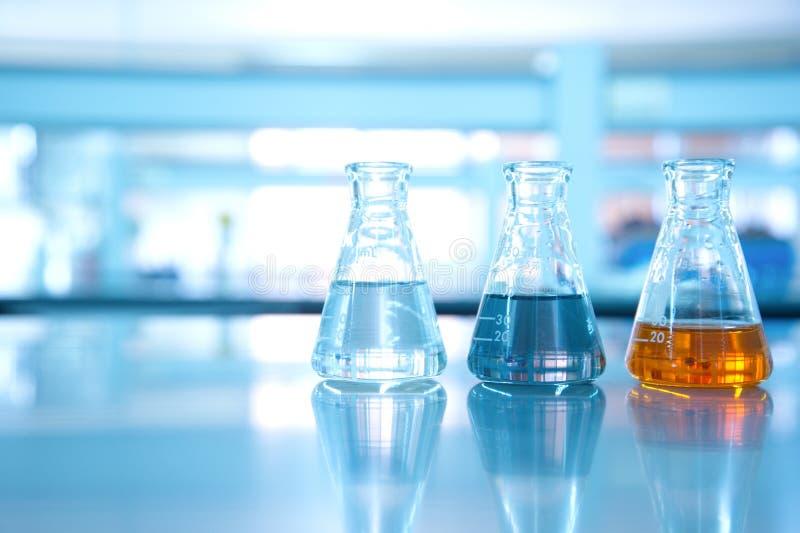 三烧瓶水黑色橙色解答在科学实验室 免版税图库摄影
