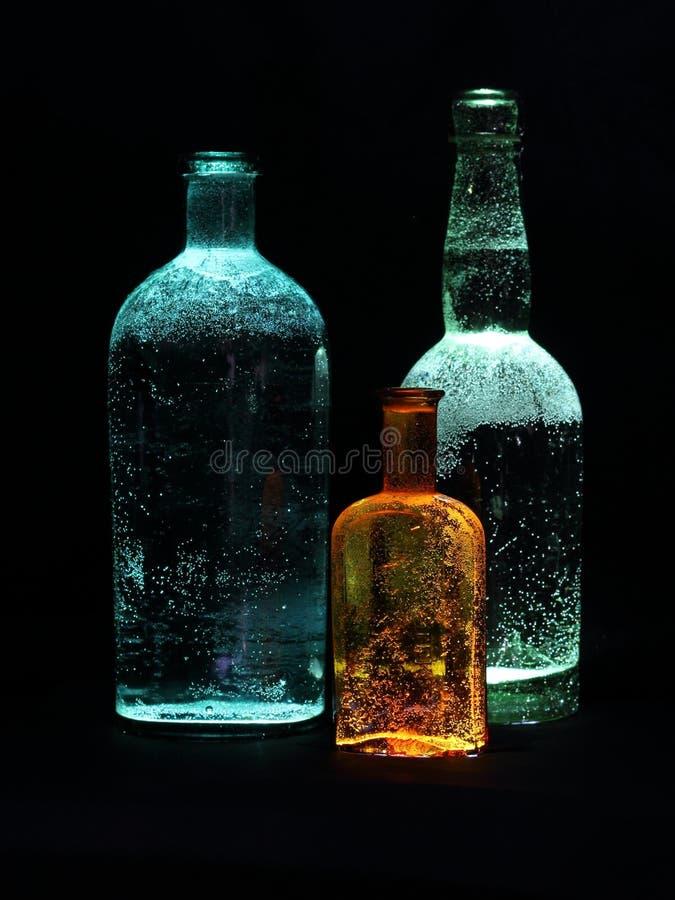 三照亮了在黑暗的玻璃瓶 库存照片