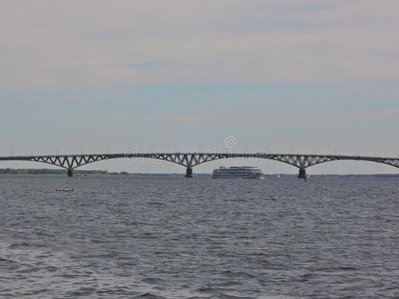 三甲板游轮风帆在一条宽蓝色河的一座大美丽的汽车桥梁下在一个清楚的夏日 免版税库存照片