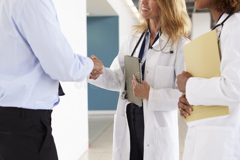 三男性和握手,中间部分的女性医生 免版税图库摄影