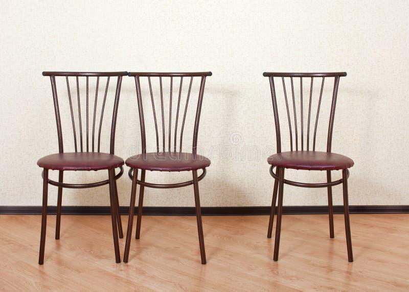 三相同椅子其次对墙壁 免版税库存图片