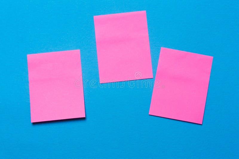 三空的桃红色笔记, noteson蓝色背景 库存图片