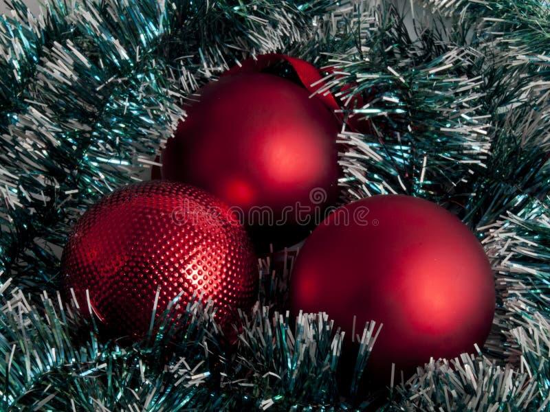 三红色在绿色闪亮金属片的圣诞节球 免版税库存照片