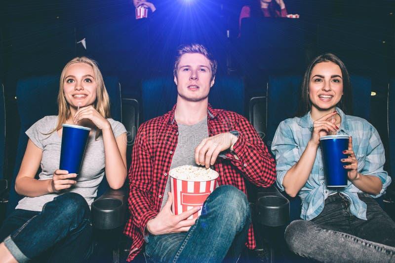 三美丽的人在椅子和观看的电影坐 他们看起来愉快和激动 女孩喝可乐 免版税库存照片