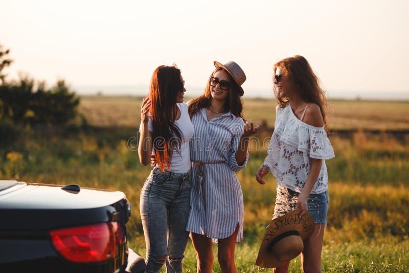 三美丽的少女在领域在汽车旁边和谈话站立在一温暖的好日子 免版税库存图片