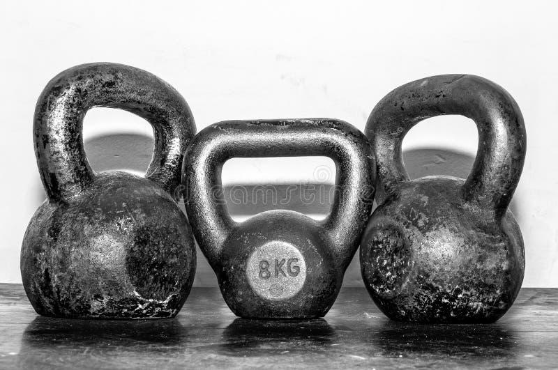 三老和在健身房地板上的生锈的水壶响铃 库存照片