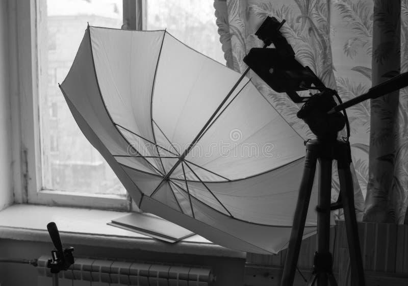 三脚架和反射器以一把白色伞的形式在老窗口的背景 免版税库存照片