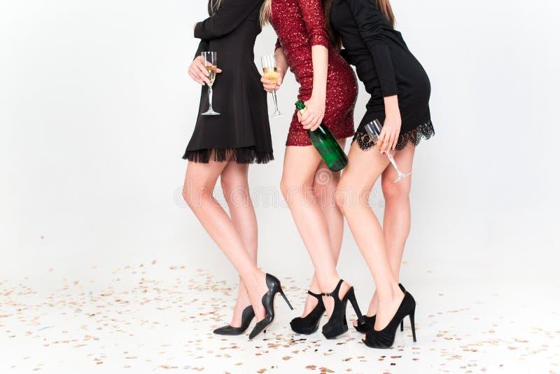 三获得乐趣,微笑,跳舞和饮用香槟在演播室的庄重装束的年轻女人的完善的长的腿 免版税库存照片