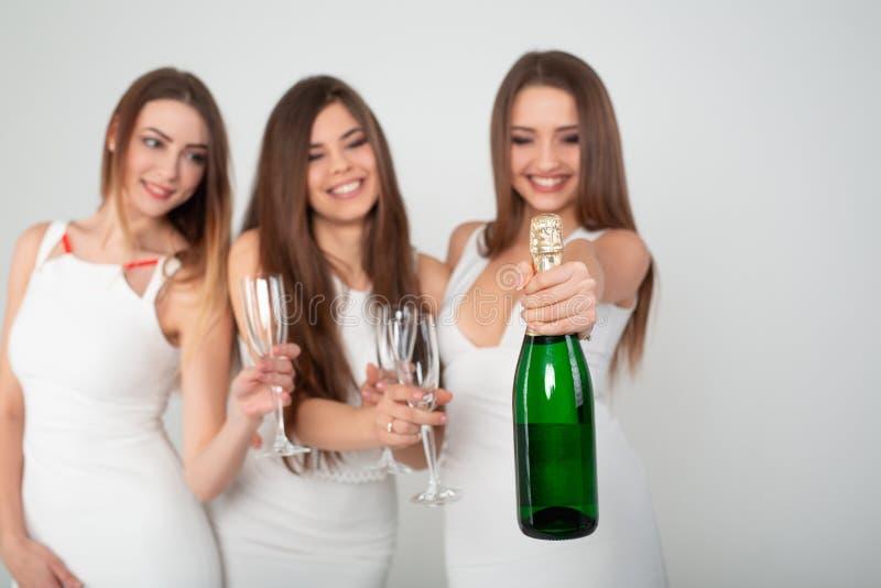 三获得乐趣,微笑,跳舞和饮用香槟在白色背景的演播室的庄重装束的年轻女人 图库摄影