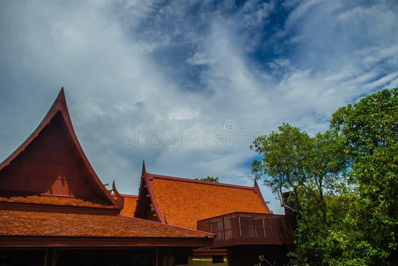 三角形屋顶在泰国样式的房子设计有蓝天背景 泰国样式木屋顶房子与蓝天的 免版税库存图片