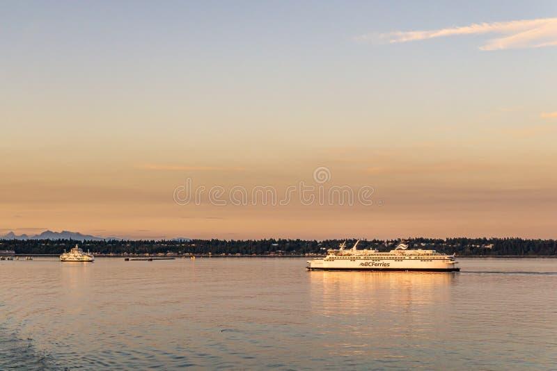 三角洲,加拿大- 2019年7月12日:在开阔水域的bcferries小船在Tsawwassen轮渡码头日落乘驾附近 免版税库存图片