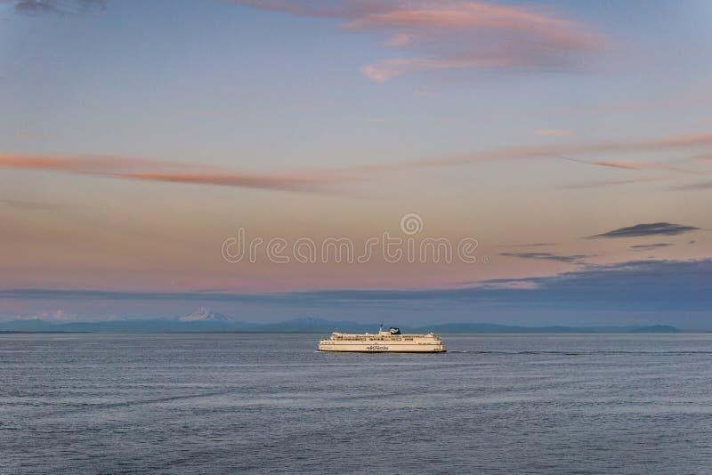 三角洲,加拿大- 2019年7月12日:在开阔水域的bcferries小船在Tsawwassen轮渡码头日落乘驾附近 库存图片