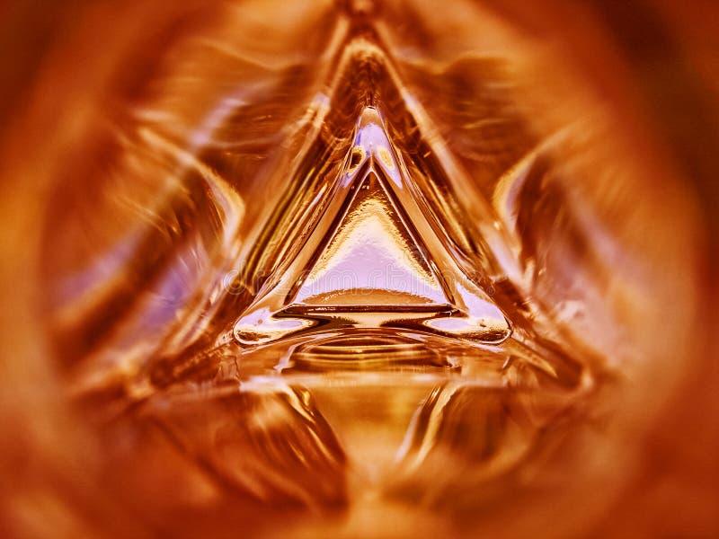 三角玻璃瓶红颜色背景的里面的抽象图象 免版税库存照片