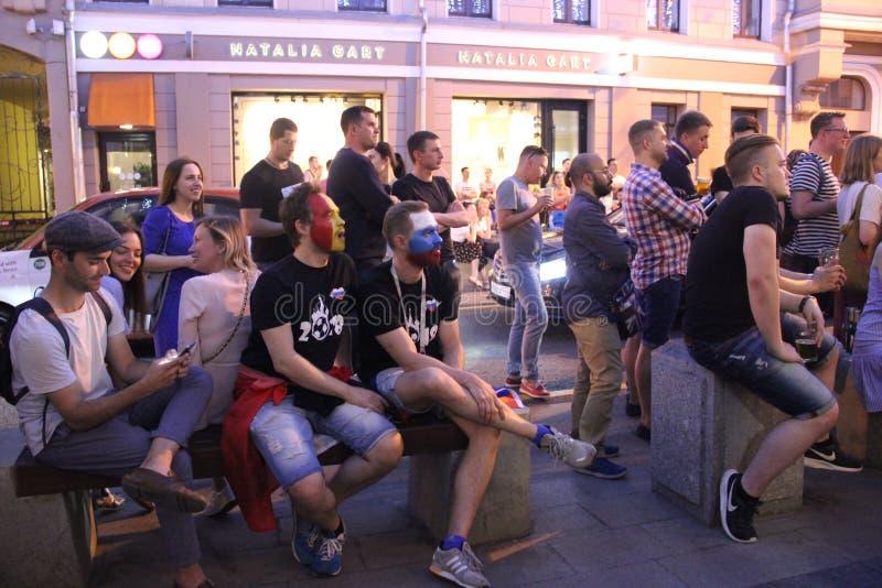 三足球迷观看在城市咖啡馆的比赛广播 免版税库存照片