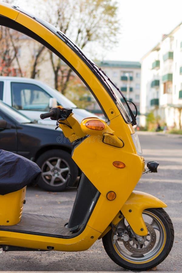 三轮机舱摩托车侧视 模糊的汽车背景 免版税图库摄影