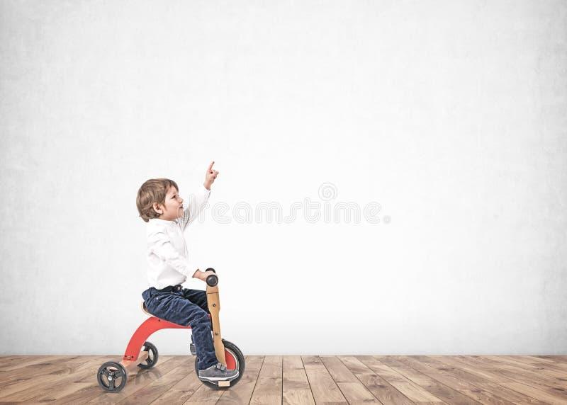 三轮车的小男孩指向在空的屋子里的 免版税库存图片