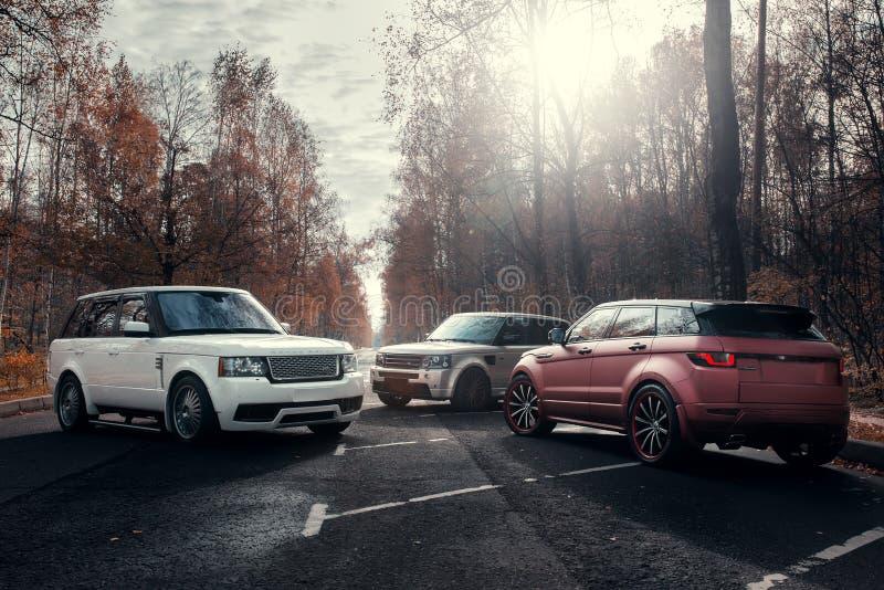 三辆汽车陆虎路华汽车停放了在秋天森林柏油路在晴朗的白天 免版税库存图片