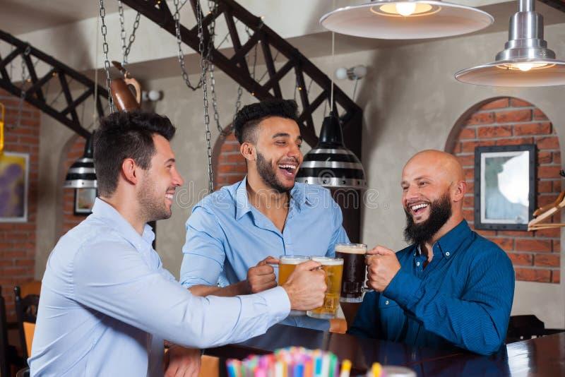 三酒吧叮当声玻璃的敬酒的人,饮用的啤酒举行杯子,混合种族快乐的朋友穿戴衬衣 图库摄影