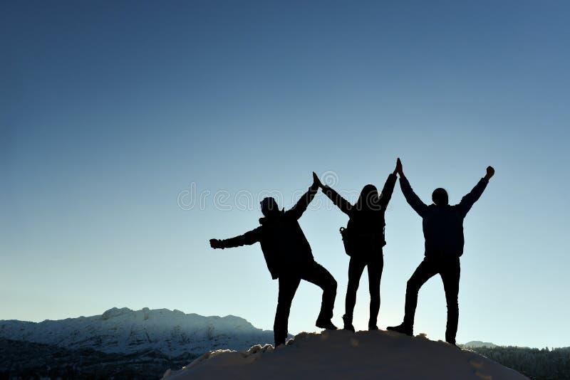 三重奏在山的胜利剪影 免版税库存照片