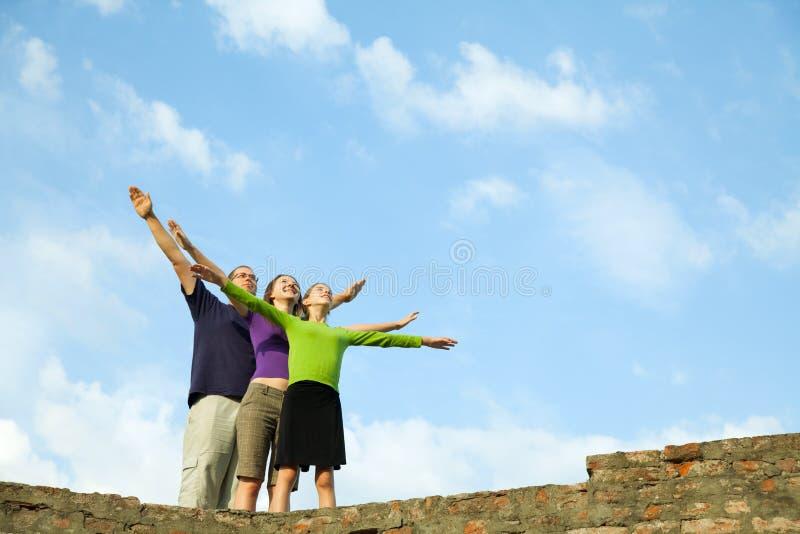三青年人和被举的手呆在一起 库存图片