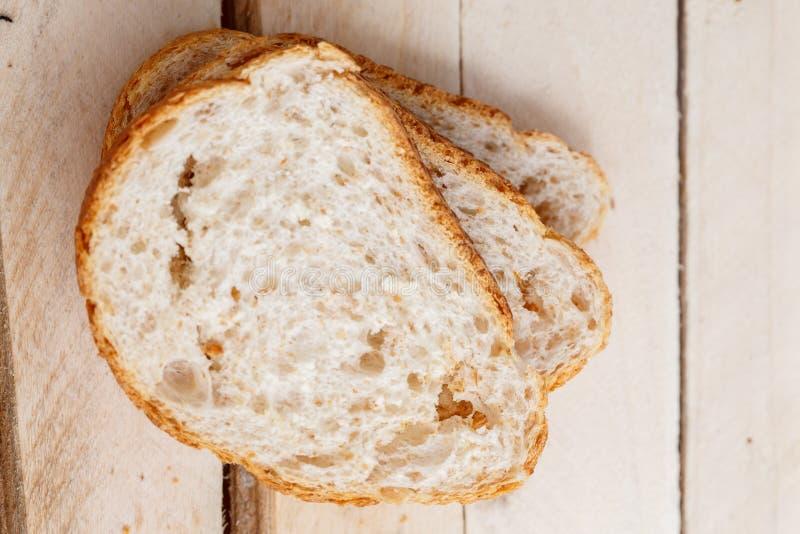 三面包片在轻的木背景的 在视图之上 免版税库存照片