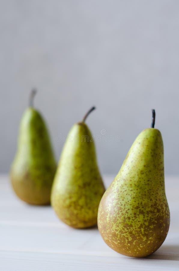 三绿色梨连续在木白色桌上 免版税图库摄影