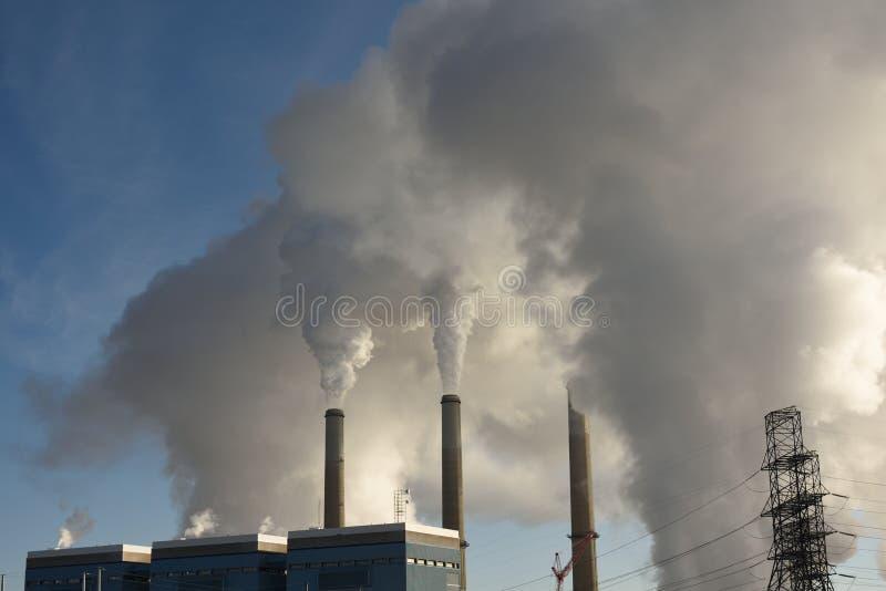 上升从一个燃煤蒸汽电动的引起的能源厂,Laramie河驻地的放射云彩  免版税图库摄影