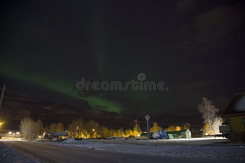 上升在一座山后的北极光极光borealis在挪威的北部的一个小村庄 冬天中 库存照片