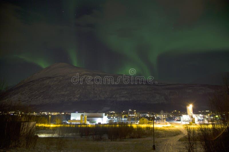 上升在一座山后的北极光极光borealis在挪威的北部的一个小村庄 冬天中 免版税库存照片