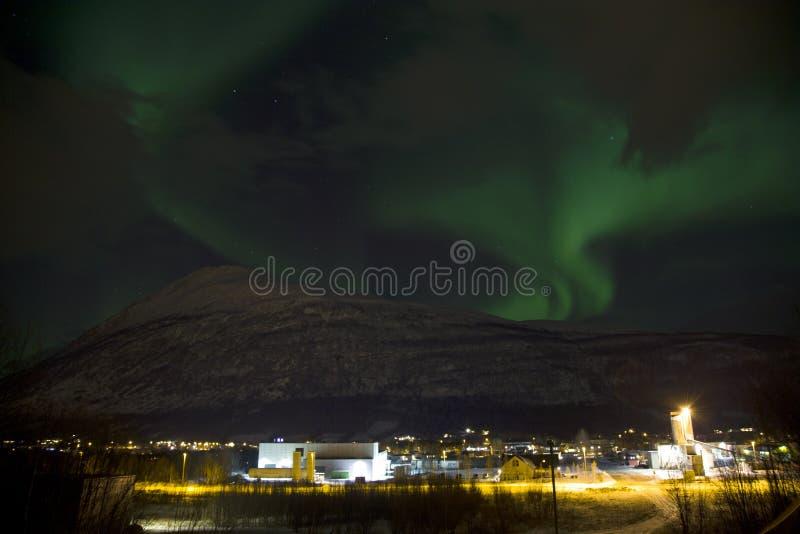 上升在一座山后的北极光极光borealis在挪威的北部的一个小村庄 冬天中 免版税库存图片