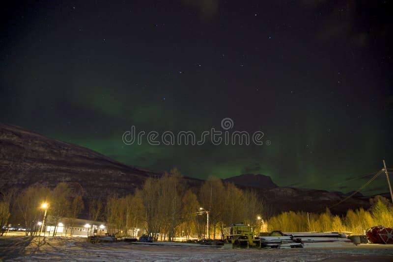 上升在一座山后的北极光极光borealis在挪威的北部的一个小村庄 冬天中 免版税图库摄影