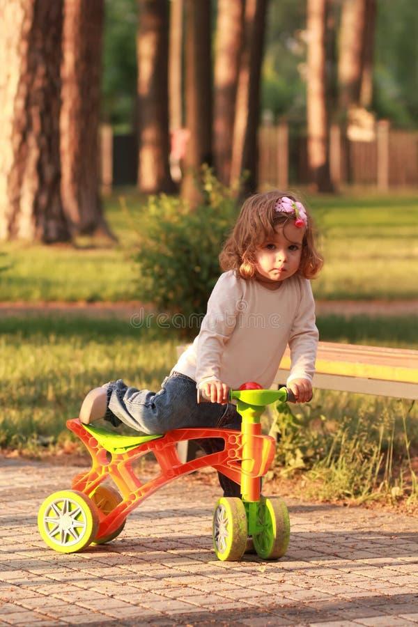 上升在一辆自行车的小小孩女孩在被日光照射了公园 免版税库存照片