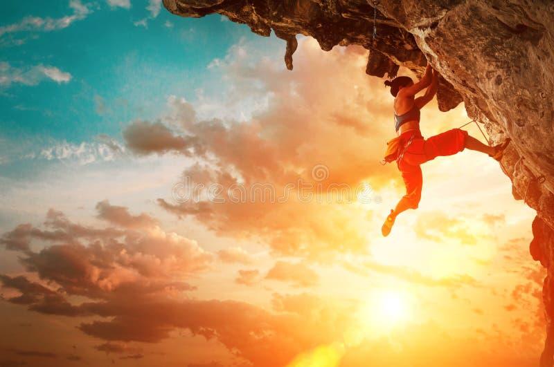 上升在伸出的峭壁岩石的运动妇女有日落天空背景 免版税库存照片