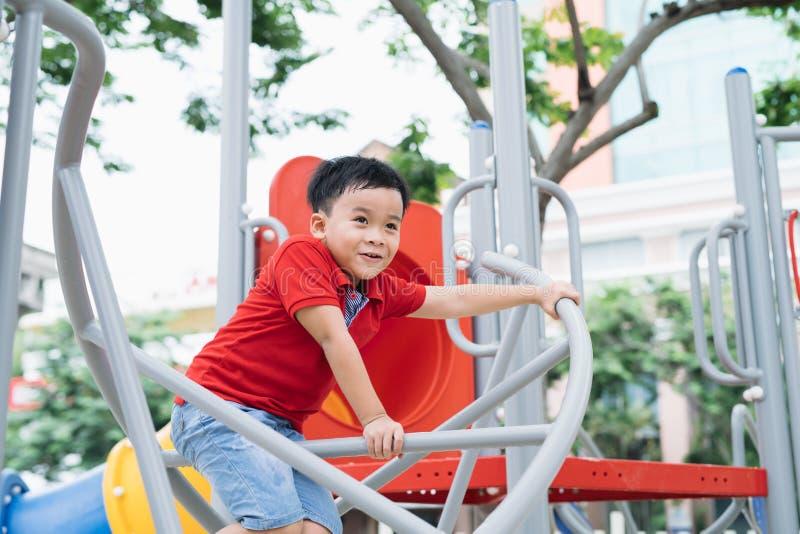 上升在儿童操场的愉快的小男孩 库存图片