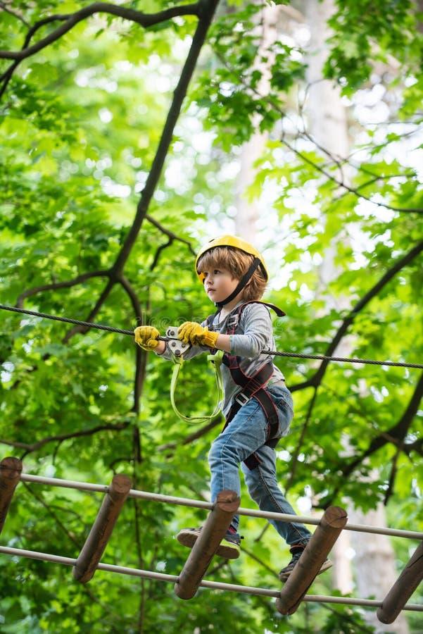 上升在冒险有盔甲和安全设备的活动公园的小孩 E ?? 免版税库存照片
