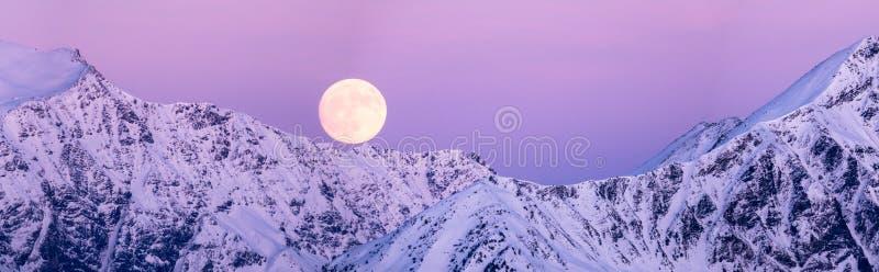 上升在冬天山风景的满月 免版税库存照片