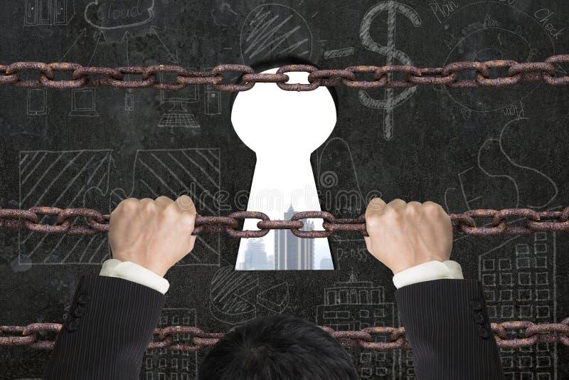上升在匙孔的铁链子的商人与城市buildin 免版税图库摄影