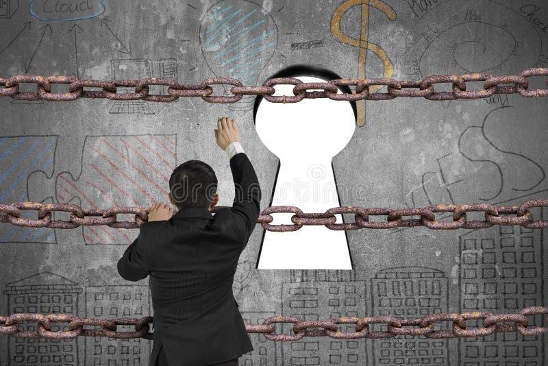 上升在匙孔的铁链子的商人与空白的白色 免版税图库摄影