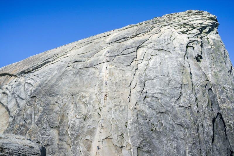 上升在半圆顶在一个晴朗的夏日,优胜美地国家公园,加利福尼亚缚住 免版税图库摄影