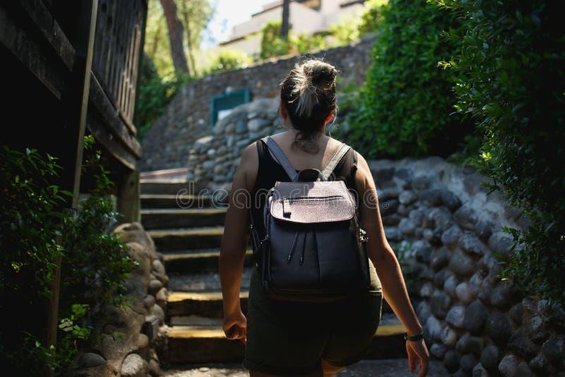 上升在古老地方小街道台阶的年轻女人  图库摄影