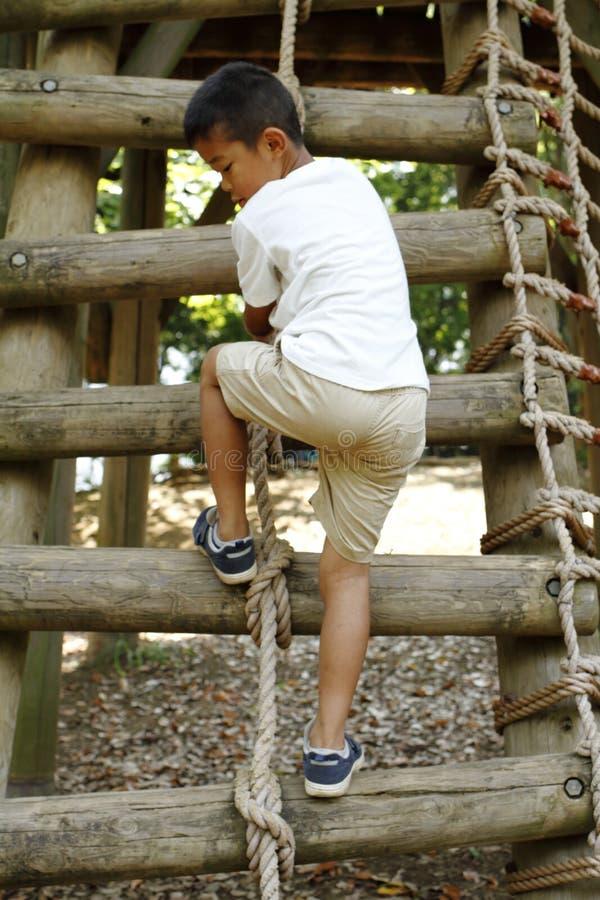 上升在墙壁上的日本男孩 免版税库存图片