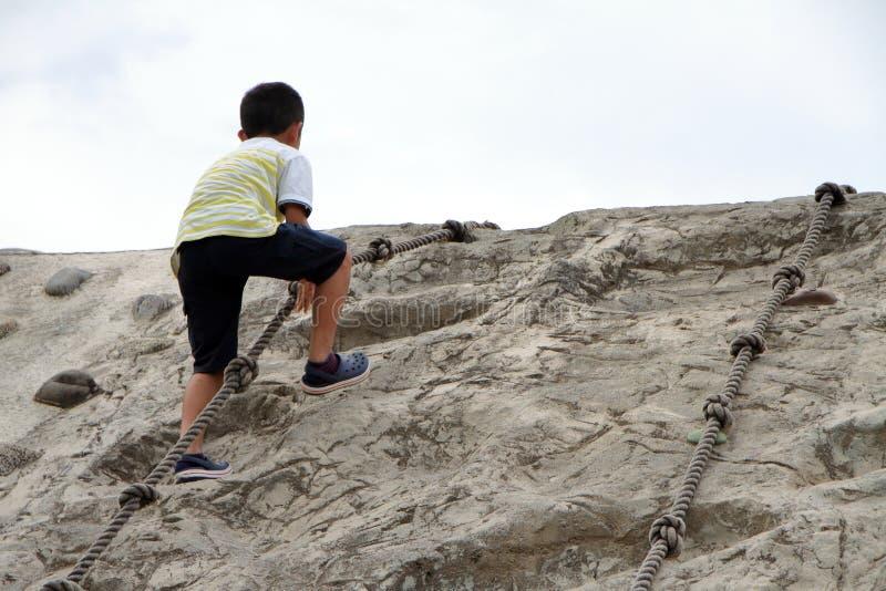上升在墙壁上的日本男孩 免版税图库摄影