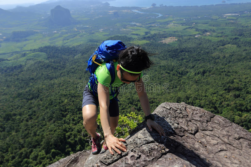 上升在山峰岩石的妇女远足者 免版税库存图片