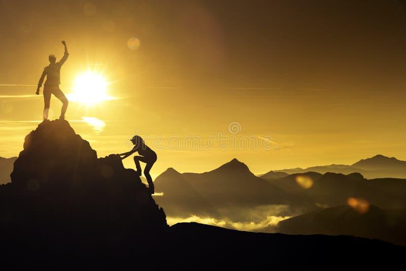 上升在山峰的两名妇女 免版税库存图片