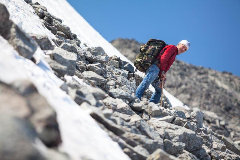 上升在山的成熟人在夏季,基于陡坡 免版税库存照片
