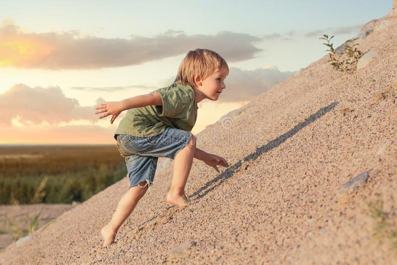 上升在山的男孩 夏日和沙丘 免版税图库摄影
