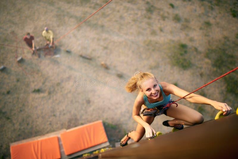 上升在岩石人为墙壁上的美丽的年轻坚强的妇女在夏天,顶视图 在系住的鞔具保险的登山人 免版税库存照片