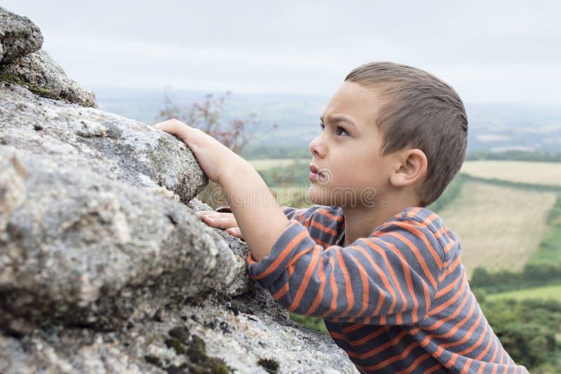上升在岩石的孩子 免版税库存图片