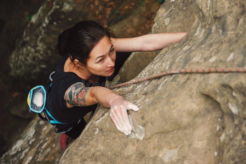 上升在岩石的美丽的少妇 库存图片