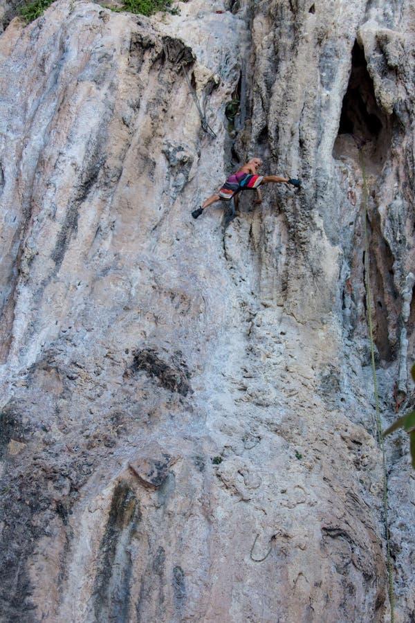 上升在岩石,在日落的山的人剪影 库存照片